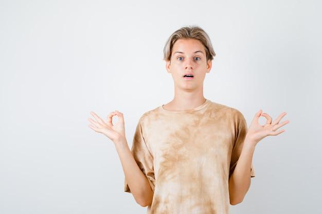 Портрет мальчика-подростка, показывающего знак мудры в футболке и выглядящего сбитым с толку, вид спереди