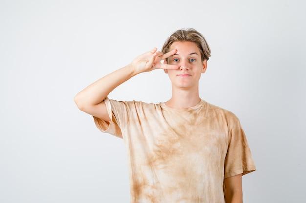 Портрет мальчика-подростка, показывающего v-знак на глазу в футболке и веселого вида спереди