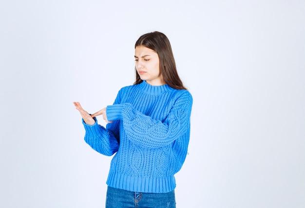 彼女の手を見て青いセーターのティーンエイジャーの女の子の肖像画。