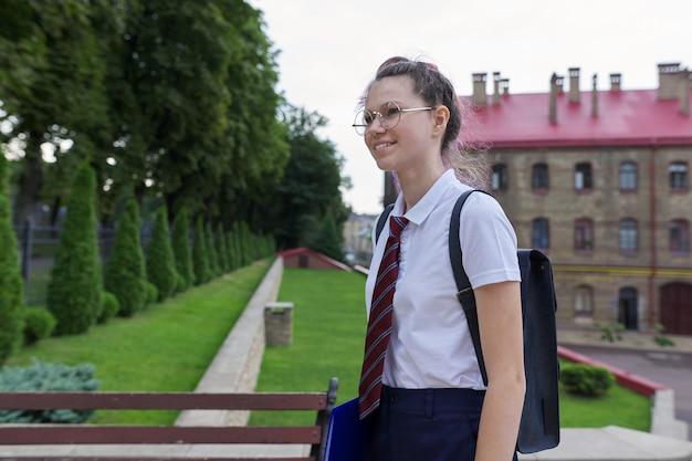 Портрет девочки-подростка с рюкзаком, идущим в школу, летним осенним утром, школьным зданием. снова в школу, обратно в колледж