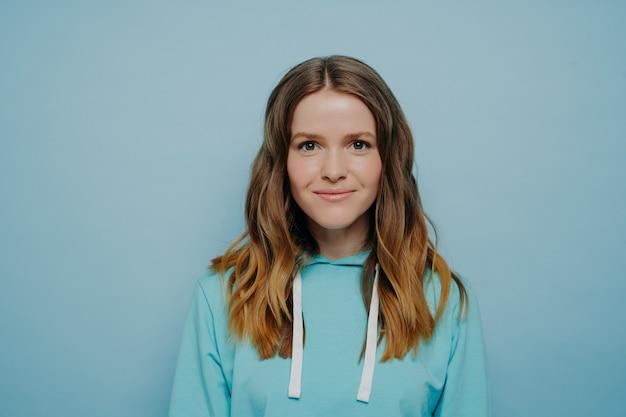 スタジオの背景に立っている快適なカジュアルな青いスウェットシャツでカメラを見ながら笑っている波状のオンブルの髪型を持つティーンエイジャーの女の子の肖像画