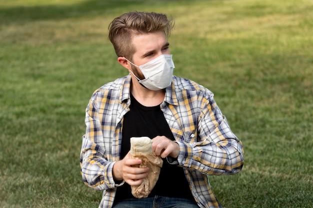Портрет подростка с маской для лица, держащего кебаб
