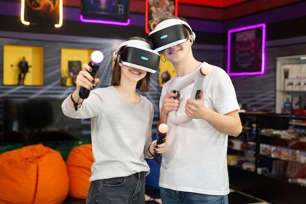 ゲーム クラブで、眼鏡をかけたバーチャル リアリティ ヘッドセットと手の動きのコントローラーを持つ 10 代の若者、男の子と女の子のポートレート。