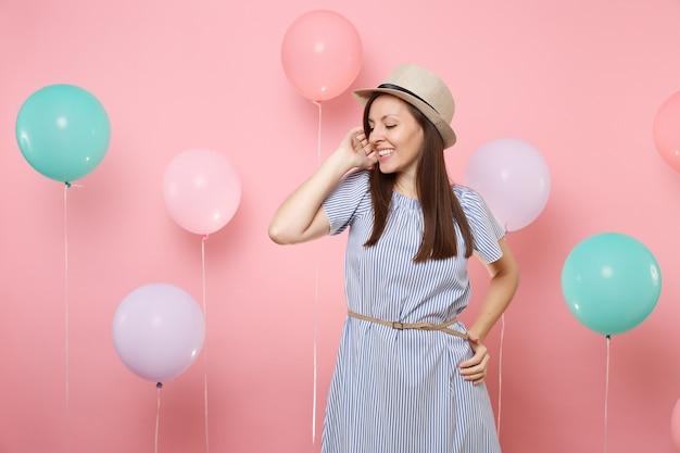 다채로운 공기 풍선과 함께 분홍색 배경에 얼굴 가까이에 손을 잡고 밀짚 여름 모자와 파란색 드레스를 입고 부드러운 매혹적인 젊은 여성의 초상화. 생일 휴일 파티 사람들은 진심 어린 감정.
