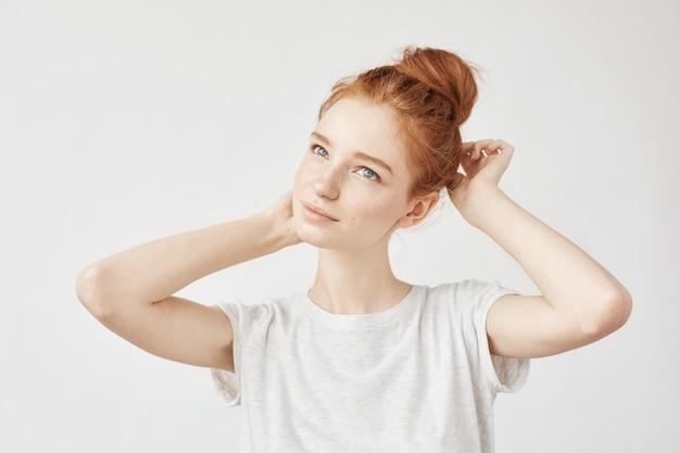髪のお団子とそばかすの笑顔で柔らかい赤毛の女性の肖像画。