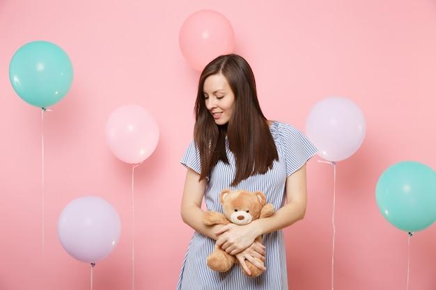 Портрет нежной улыбающейся молодой женщины в голубом платье, держащей и обнимающей плюшевую игрушку плюшевого мишку на розовом фоне с красочными воздушными шарами. праздник дня рождения, концепция искренних эмоций людей.
