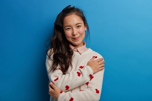 부드러운 젊은 아시아 소녀의 초상화는 편안함과 평온함을 느끼고, hersellf를 안아주고, 부드럽게 미소 짓고, 부드러운 점퍼를 입고, 파란색 벽에 고립 된 긍정적 인 감정을 표현합니다.