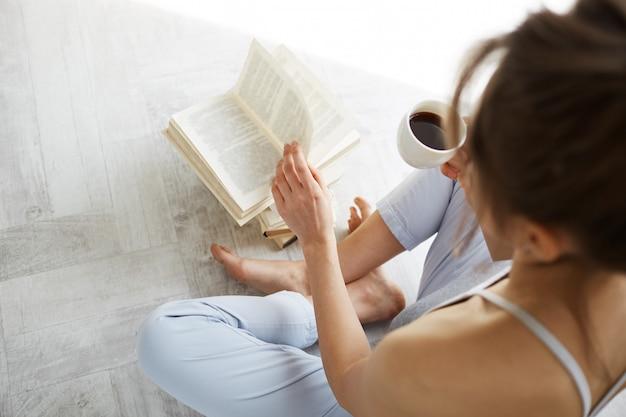 白い壁の上の床に座ってコーヒーのカップを保持している本を読んで柔らかい若い美しい女性の肖像画。