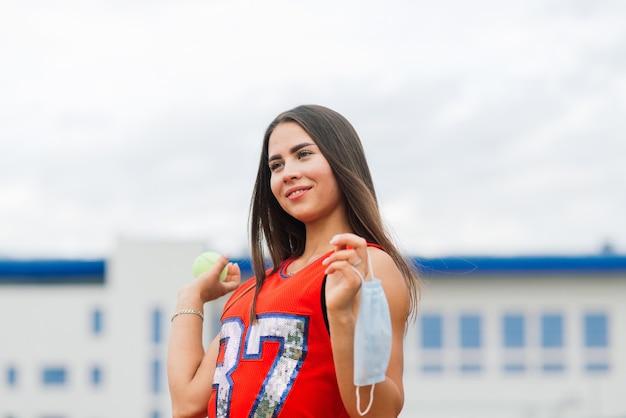 保護マスクで外でボールを保持しているテニスプレーヤーの女の子の肖像画