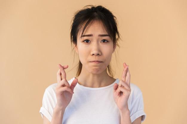 神を懇願する基本的なtシャツを着ている緊張したアジアの女性の肖像画は、スタジオでベージュの壁の上に分離された指を交差させてください