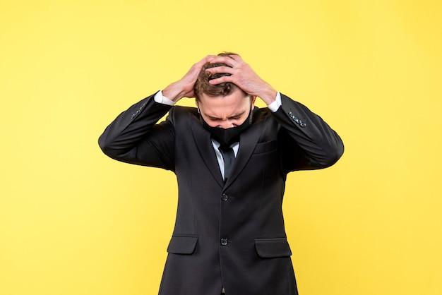 Портрет напряженного молодого бизнесмена на желтом