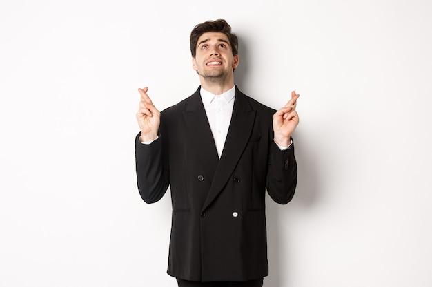 緊張して心配しているハンサムなビジネスマンの肖像画、指を交差させて見上げる、神を懇願する、願い事をする、黒いスーツを着て白い背景に立っている。