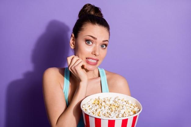 Портрет напуганной девушки, поедающей кукурузу, смотрит фильм в жанре триллера