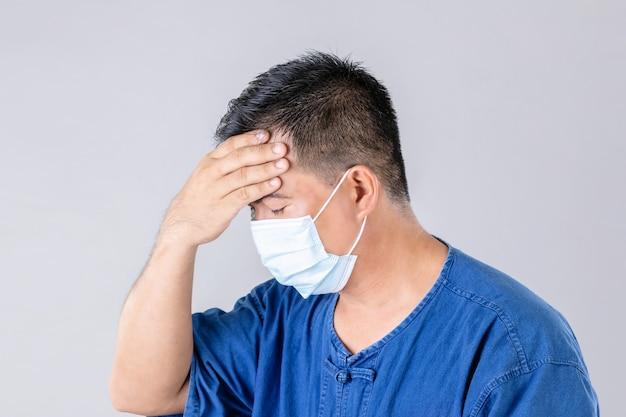 ウイルスを防止し、頭に触れるために防護マスクを着用しているタイの農家の肖像画