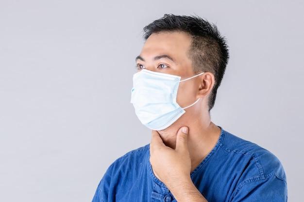 ウイルスを防ぎ首に触れるために保護マスクを着用しているタイの農家の肖像画