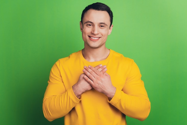 緑の背景に感謝の気持ちを込めて男の手胸の歯を見せる笑顔の肖像画