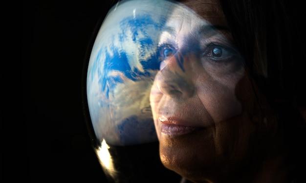행성 지구를 보고 있는 성인 여성 우주 비행사의 초상화
