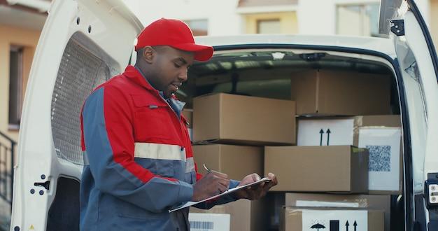 Портрет афро-американских молодых мужчин работника судоходной компании, стоя у фургона с коробками и написание документа, а затем улыбаясь в камеру. на улице.