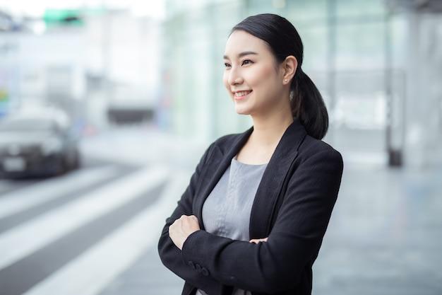 사무실에서 팔짱을 끼고 멀리 바라보는 아름다운 아시아 여성 사업가의 초상화