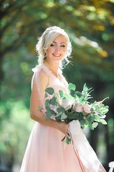 自然の中で花の花束を持つ美しい花嫁の肖像画。ファインアート写真。