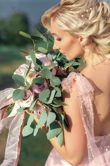 자연 속에서 꽃의 부케와 함께 아름 다운 신부의 초상화. 미술 사진.