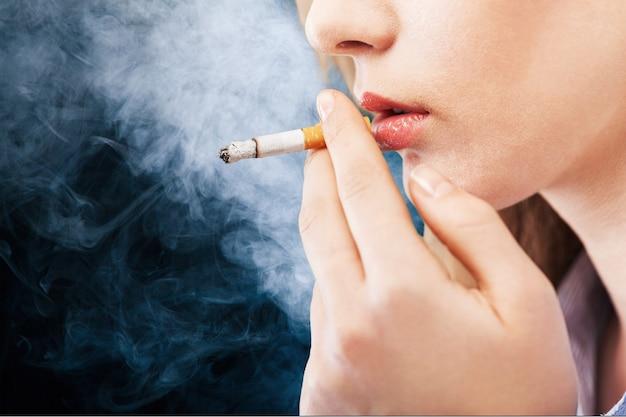 孤立した美しいエレガントな女の子喫煙タバコの肖像画