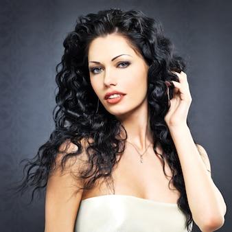 長い巻き毛の髪型のポーズ屋内で美しいファッションセクシーな女性の肖像画