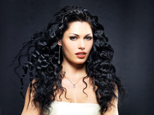 長い巻き毛の髪型を持つ美しいファッション女性の肖像画は屋内でポーズをとる