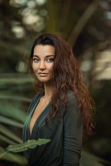 정글에 서있는 자연스러운 메이크업과 젖은 머리카락을 가진 아름다운 그을린 소녀의 초상화