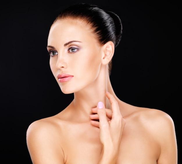 손으로 목을 만지는 아름다운 여자의 초상화-흰색에 고립