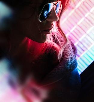 아름 다운 젊은 프로 게이머 소녀의 초상화입니다. 네온 불빛으로 안경을 쓴 매력적인 소녀.