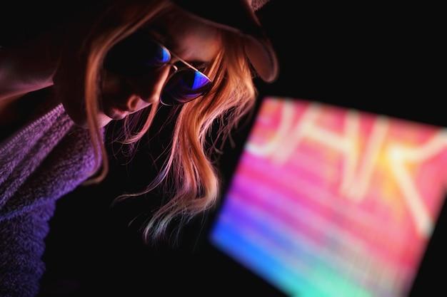 美しい若いプロゲーマーの女の子の肖像画。ネオンライトによるメガネの魅力的な女の子。