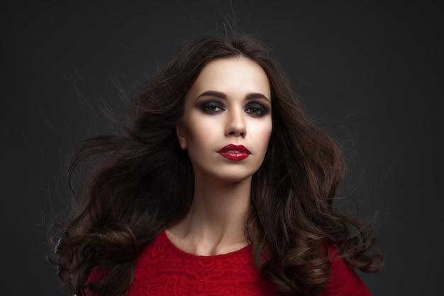스튜디오에서 포즈를 취하 긴 갈색 머리를 가진 아름 다운 젊은 여자의 초상화