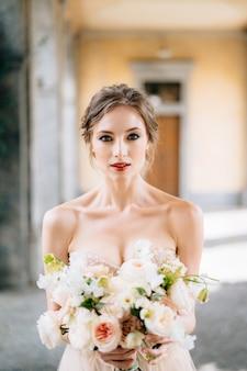 アーチ型の部屋でピンクの花の花束とドレスを着た花嫁の肖像画コモ湖イタリア