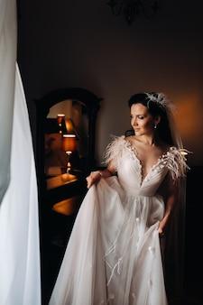 鏡の近くの家の内部のウェディングドレスの花嫁の肖像画