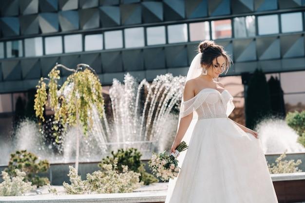 噴水の近くの街の花嫁の肖像画。巻き毛の見事な若い花嫁。