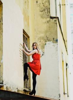 建物の壁にポーズをとって街の女の子の肖像画
