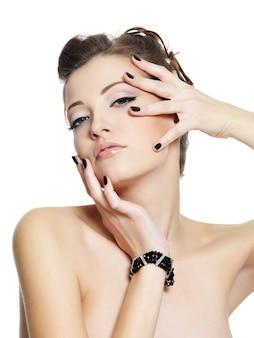 白でポーズをとって黒い爪を持つ魅力的な若い女性の肖像画