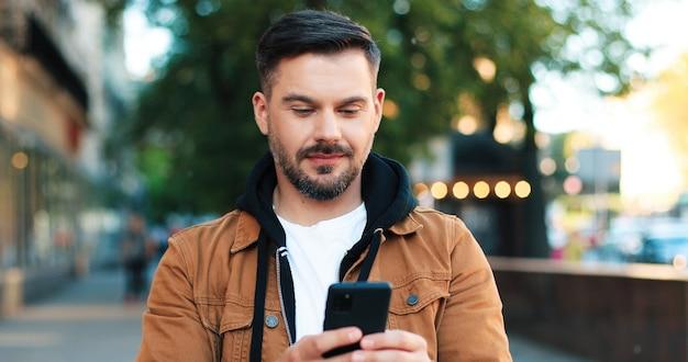 通りで彼のスマートフォンを持って歩いている間、魅力的な笑顔と健康な歯を示すハンサムな白人男性の肖像画。人とガジェットの概念