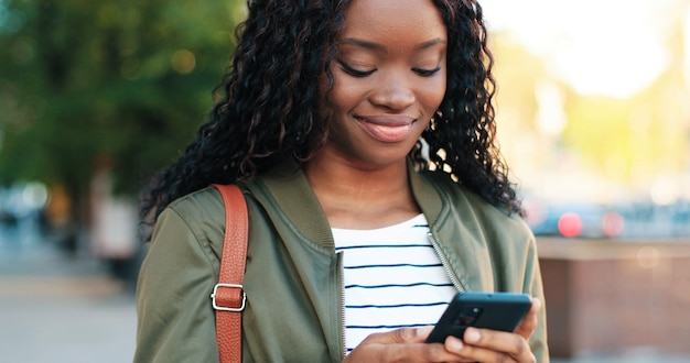通りで彼女のスマートフォンを持って歩いている間魅力的な笑顔と健康な歯を示すハンサムな多民族の女性の肖像画。人とガジェットの概念