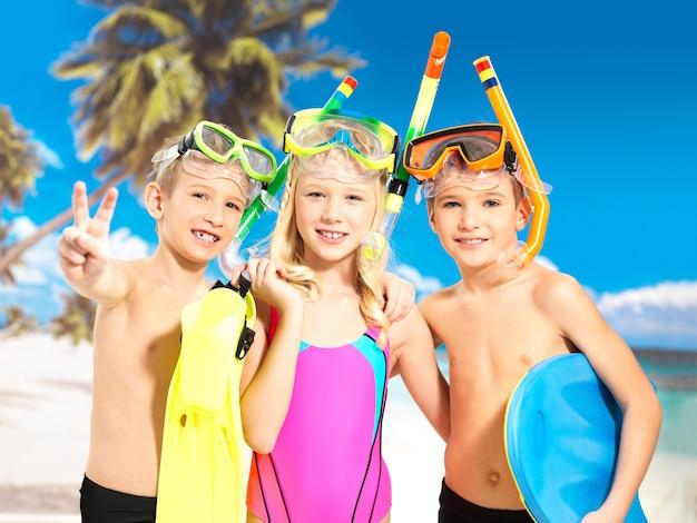 ビーチで楽しんでいる幸せな子供たちの肖像画。頭に水泳マスクを付けた明るい色の水着で一緒に立っている小学生の子供たち。