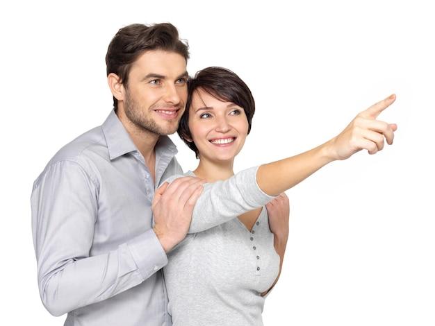 遠くを見て、指している幸せなカップルの肖像画、。