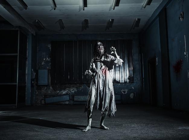 怖い地下室にいるホラーゾンビの女性の肖像画。ハロウィーン。