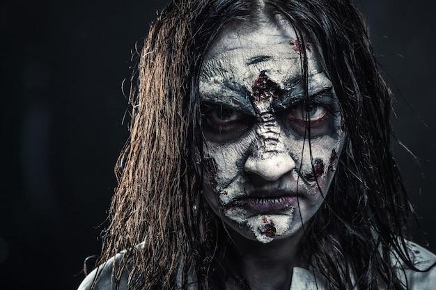 血まみれの顔を持つホラーゾンビの女性の肖像画。ハロウィーン。怖い。