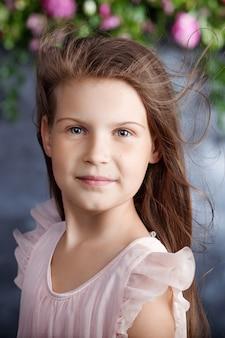 꽃의 부케와 함께 사랑스러운 어린 소녀의 초상화. 머리카락에 바람