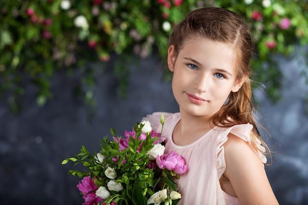 꽃의 부케와 함께 사랑스러운 어린 소녀의 초상화.