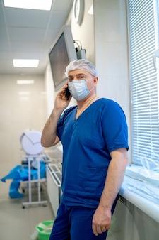 전문 외과 의사의 초상화입니다. 마스크를 쓴 의사. 전문 장비 근처에 서 있는 남자.