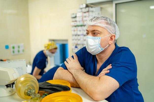 Портрет профессионального хирурга. доктор в маске. врач сидит возле профессионального оборудования.