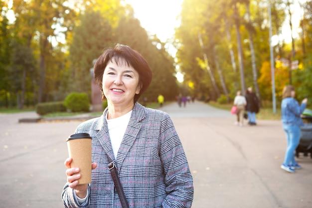 그녀와 함께 재사용 가능한 플라스틱 컵과 함께 공원에 있는 senora의 초상화. 재활용 및 생태학, 폐기물 제로. 맑은 공기 속을 걷는 50년의 행복한 나이