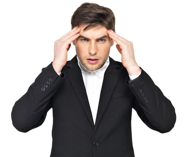 頭に手を持って考えるビジネスマンの肖像画。重いストレスにさらされている若い男の肖像画